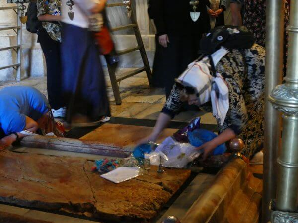Tourists placing souvenirs on the Stone of Annointing in the Church of the Holy Sepulchre